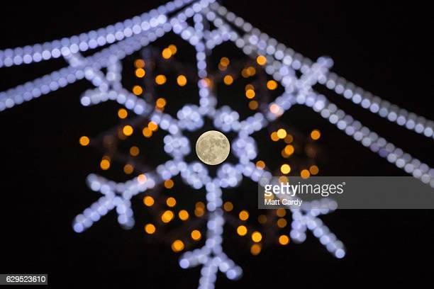 Clouds clear to allow a view of the final full moon of the year a socalled 'Cold Moon' as it appears behind Christmas lights decorating Penzance main...