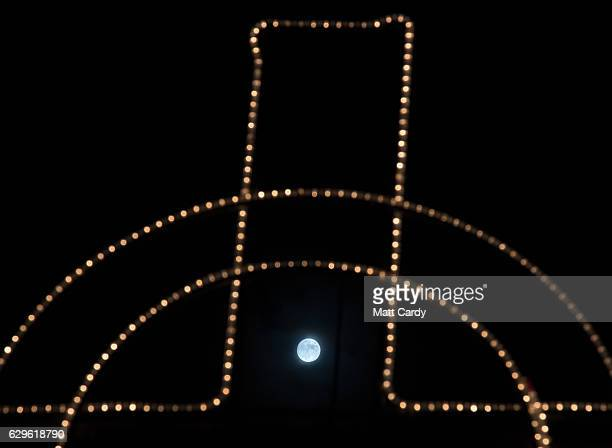 Clouds clear to allow a view of the final full moon of the year a socalled 'Cold Moon' as it appears behind Christmas lights decorating Marazion on...