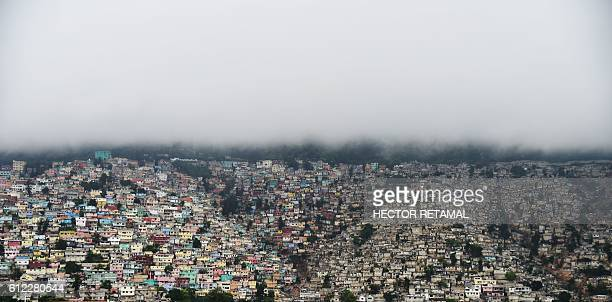 TOPSHOT Clouds cover the mountains of Petion Ville rain fall in the Haitian capital of PortauPrince on October 3 2016 Hurricane Matthew has left one...