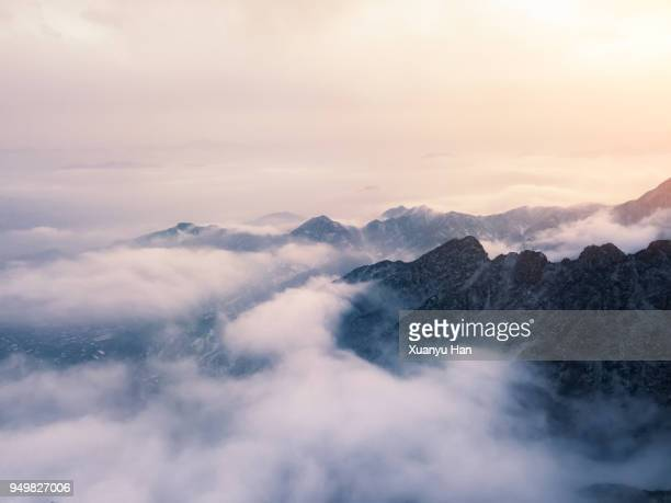 clouds drift amid rocky cliffs. - mountain range stock pictures, royalty-free photos & images