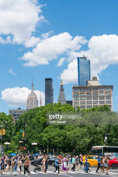 Clouds float over the green forest of Union Square Park at Manhattan New York NY USA on Jun. 26 2017. People cross the 4th Avenue and cars run on the 14the street.