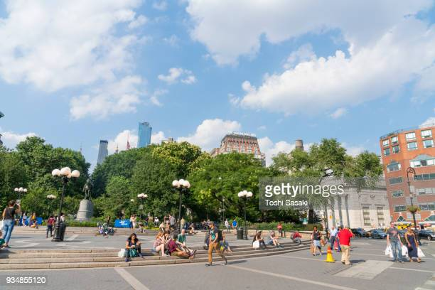 clouds float over the green forest of union square park at manhattan new york ny usa on aug. 08 2017. people walk around the park. - union square new york city stock pictures, royalty-free photos & images