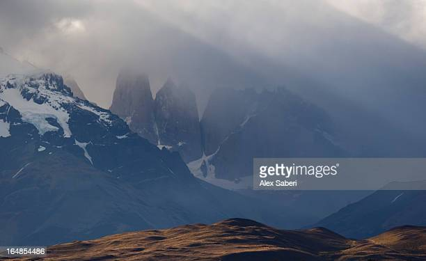 clouds form over the torres del paine mountains in chile. - alex saberi stock-fotos und bilder