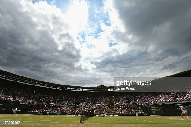 Clouds gather over Court One as Novak Djokovic of Serbia plays a backhand during the Gentlemen's Singles quarterfinal match against Tomas Berdych of...