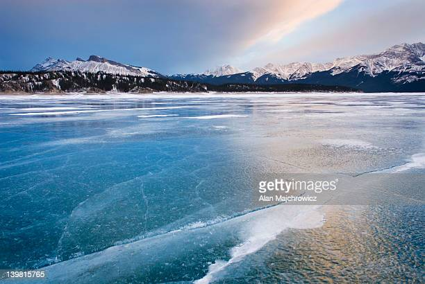 Clouds glowing in a winter sunset over the wind polished ice of Abraham Lake, Alberta, Canada
