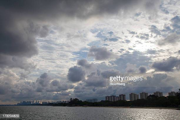 Clouds hang over buildings in the central business district left in Singapore on Tuesday July 9 2013 Singapore will release secondquarter gross...