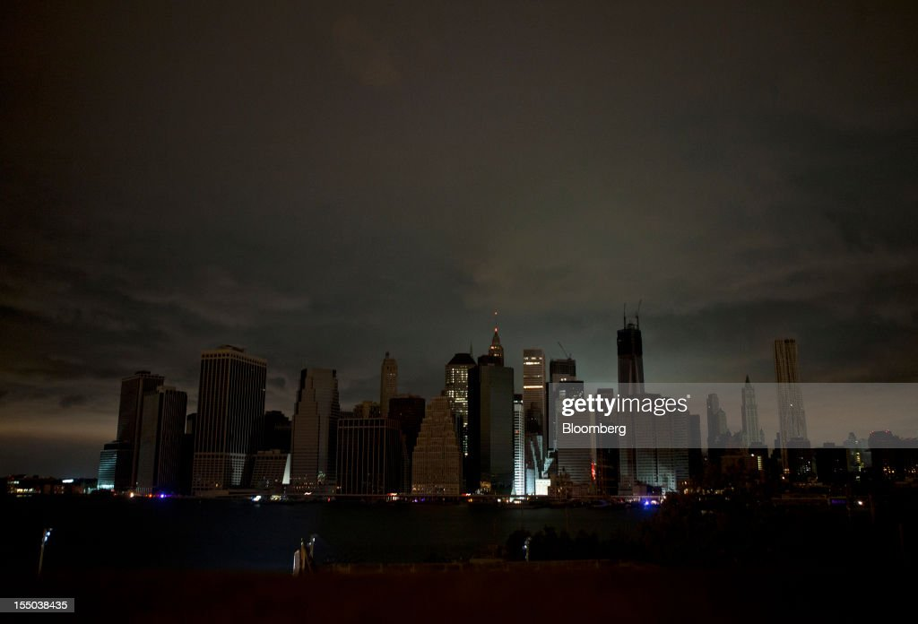 Clouds hang over the darkened lower Manhattan skyline at night in New York, U.S., on Tuesday, Oct. 30, 2012. New York City officials spent the day grappling with the damage from Sandy, the Atlantic superstorm that killed 10 people, sparked a fire that destroyed 111 homes in Queens, flooded tunnels of the biggest U.S. transit system and left more than 750,000 customers without power. Photographer: Victor J. Blue/Bloomberg via Getty Images
