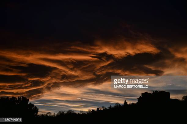 Clouds hover as the sun sets in Manta, Cuneo, northwestern Italy on March 15, 2019.