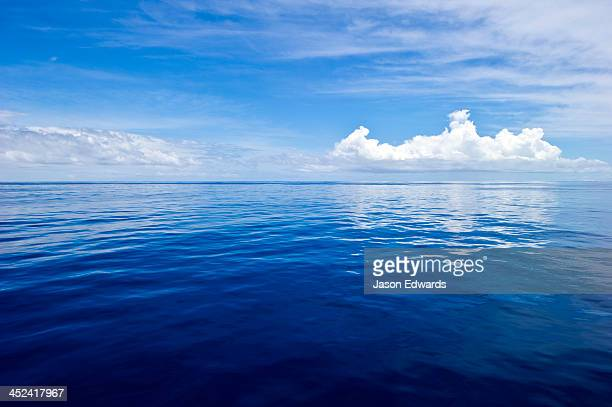 Clouds hovering over a deep blue dead calm tropical sea.