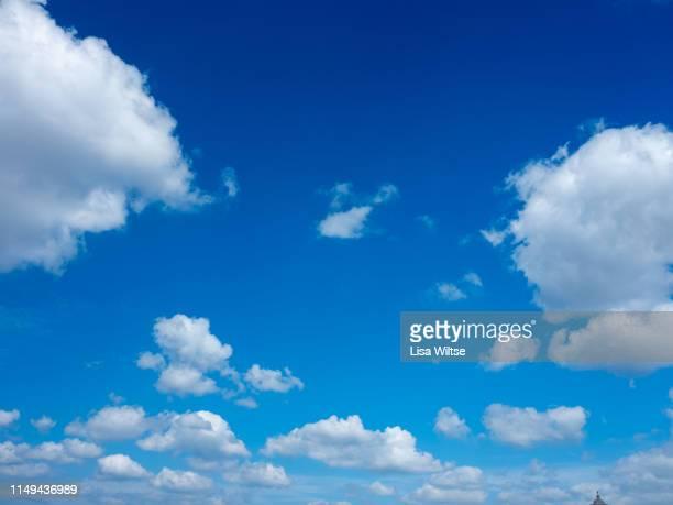clouds in a bright blue sky - heldere lucht stockfoto's en -beelden