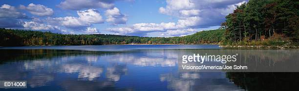 clouds mirrored in lake surface - walden pond stock pictures, royalty-free photos & images