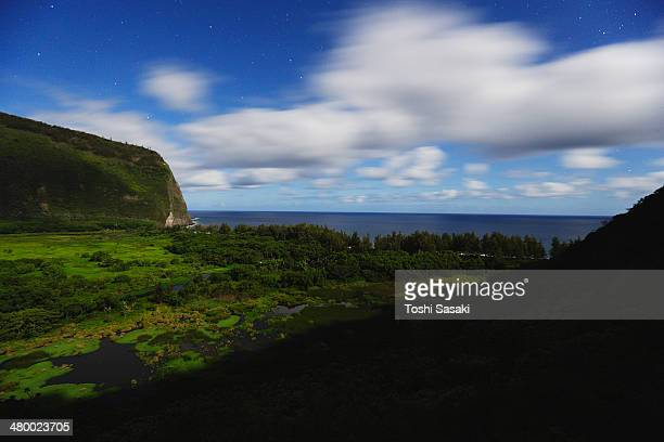 clouds moving above waipio valley at moon night - waipio valley stockfoto's en -beelden