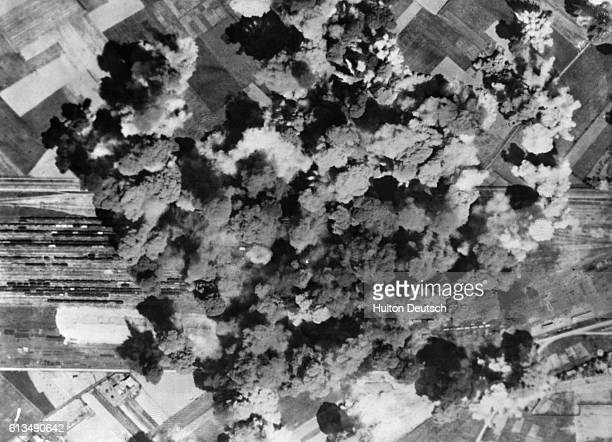 Clouds of smoke billow upwards from the railroad yard at Venissieu near Lyon following direct strikes by B17 Flying Fortress bombers of the 15th...