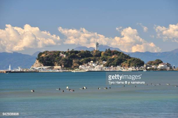 Clouds on Izu Peninsula and Enoshima Island, and many surfers on Sagami Bay, Northern Pacific Ocean in Japan