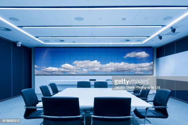 Clouds on visual screen in modern conference room