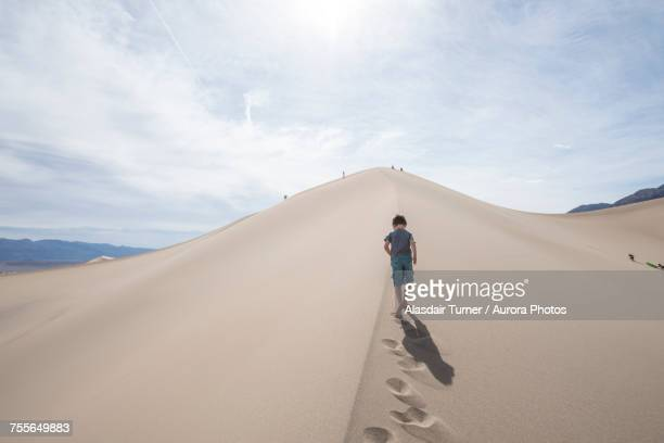 Clouds over boy walking on Mesquite Flat Sand Dunes in Death Valley National Park, California, USA
