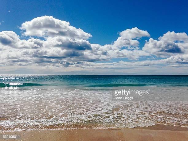 clouds over calm ocean water at the beach - water's edge stock pictures, royalty-free photos & images