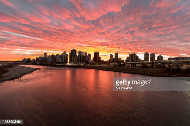 clouds over cityscape at sunset, canada - image stock pictures, royalty-free photos & images