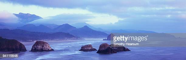clouds over coastal rocks and mountains - timothy hearsum stock photos and pictures