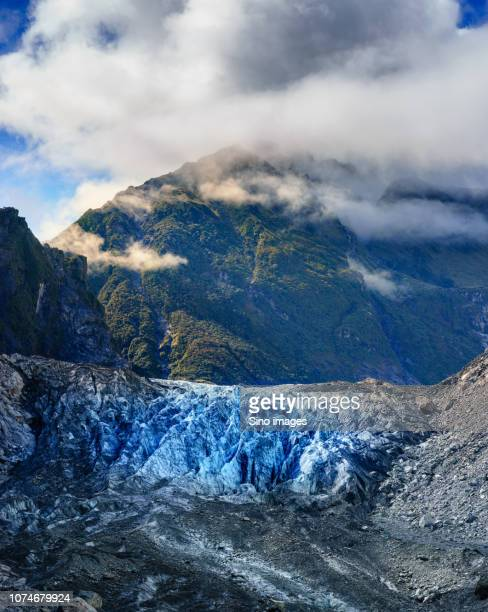 clouds over forested mountain, new zealand - image stock pictures, royalty-free photos & images