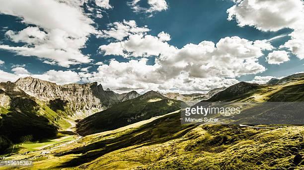 clouds over grassy rural landscape - 岩壁 ストックフォトと画像