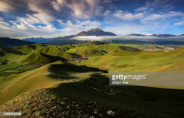 clouds over green hills, qinghai, china - image stockfoto's en -beelden