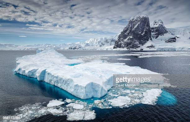 clouds over iceberg floating on water, antarctica - 氷河 ストックフォトと画像