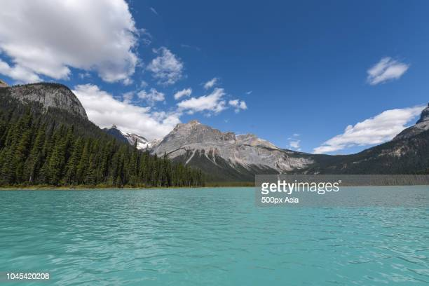 clouds over mountains and lake, canada - image stock pictures, royalty-free photos & images