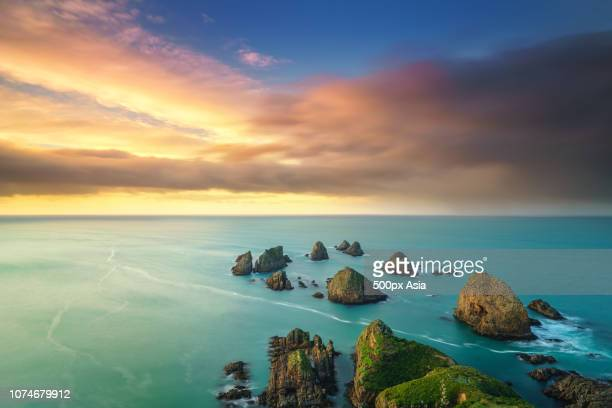 clouds over pacific ocean and coastal cliffs at dusk, new zealand - image stockfoto's en -beelden
