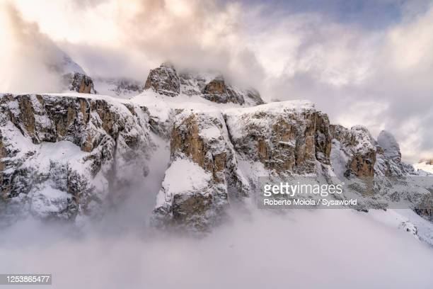clouds over pisciadu and sella group in winter, dolomites - european alps stock pictures, royalty-free photos & images