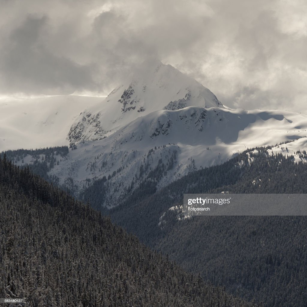 Clouds over snow covered mountains : Stock Photo
