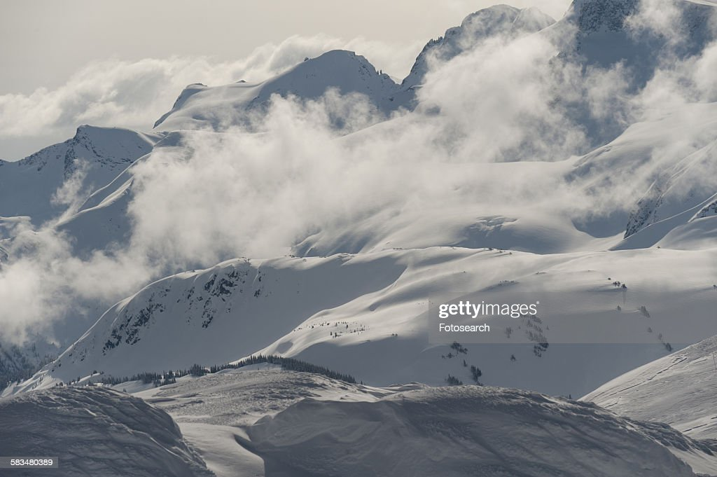 Clouds over snowcapped mountains : Stock Photo