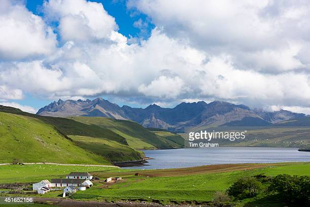 Clouds over the Cuillin mountain range with croft farm and Loch Harport near Coillure on Isle of Skye in the Highlands and Islands of Scotland.