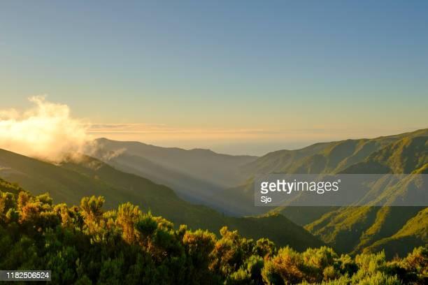 nubes sobre las montañas cerca de rabaal en la isla de madeira durante la puesta del sol - madeira fotografías e imágenes de stock