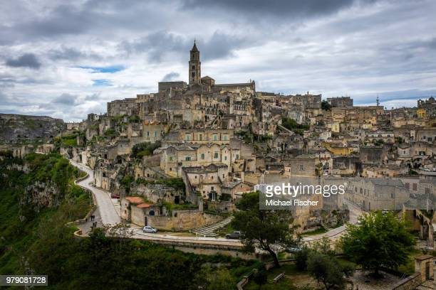 clouds over town on hill, matera, basilicata, italy - matera italy stock pictures, royalty-free photos & images