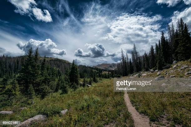 clouds over trail in rocky landscape - fort collins stock pictures, royalty-free photos & images