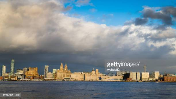 clouds pass over the liverpool skyline - liverpool england stock pictures, royalty-free photos & images