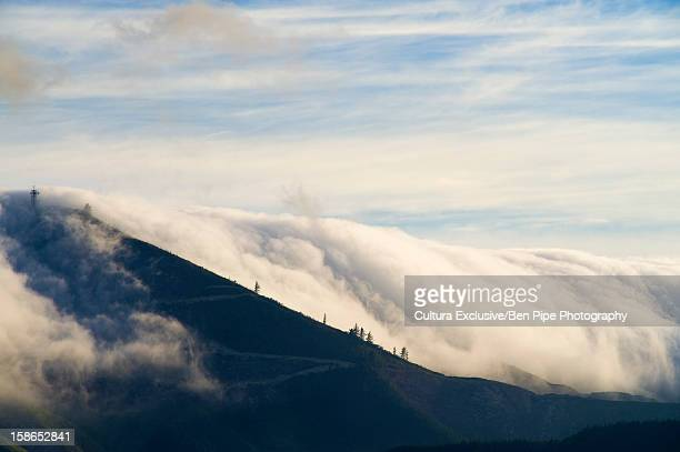 Clouds pouring over rural hillside