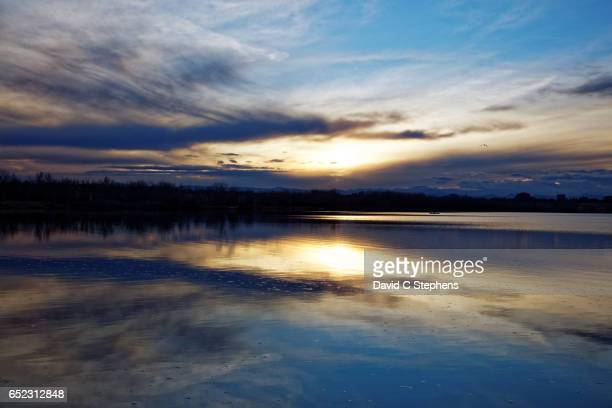 Clouds Reflect On Calm Lake At Sundown