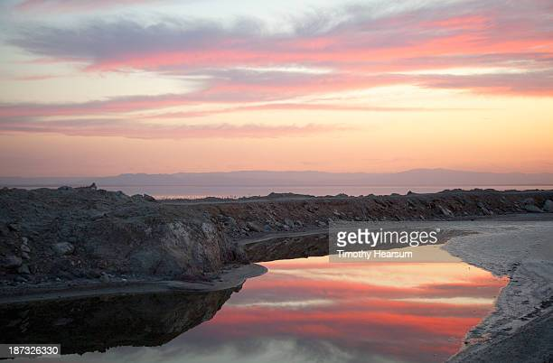 clouds reflected in inlet at sunset - timothy hearsum stock pictures, royalty-free photos & images