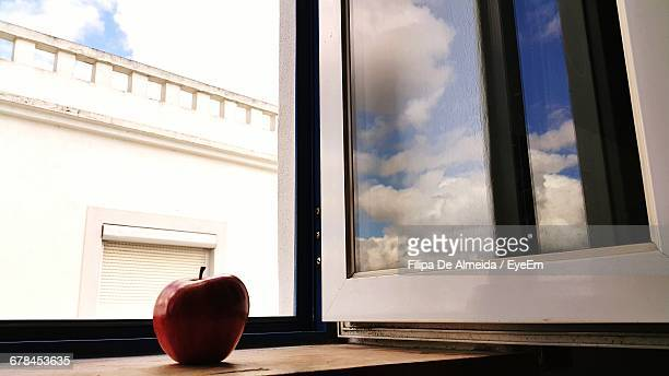 Clouds Reflecting On Glass By Apple On Window Sill At Home