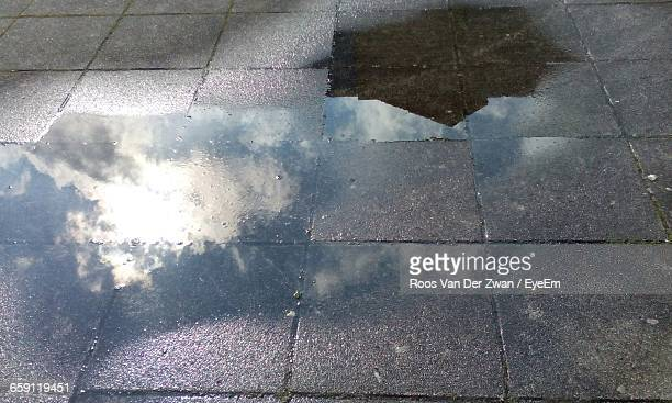 Clouds Reflecting On Puddle At Paved Street