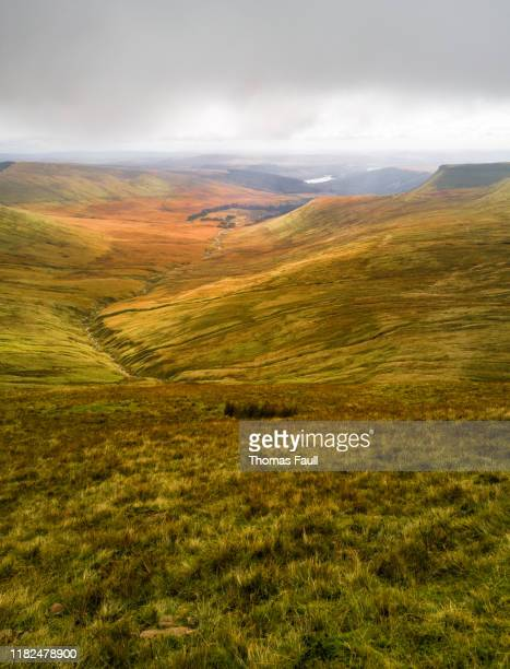 clouds roll in over the 'pen y fan' mountains in wales - wales stock pictures, royalty-free photos & images