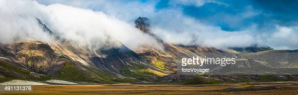 Clouds rolling over dramatic mountain panorama to valley below Iceland