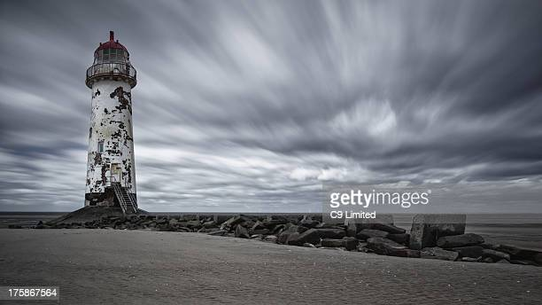 Clouds rush past the lighthouse on Talacre beach in Flintshire, Wales.