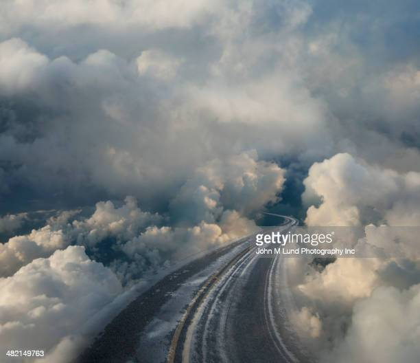 clouds surrounding winding highway - surrounding stock pictures, royalty-free photos & images