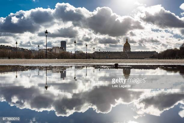 clouds wet mirror on invalides - lagarde stock photos and pictures