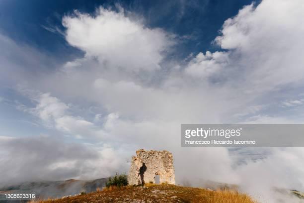 cloudscape and ruin with door, sky and landscape. wild abruzzo, italy - parco nazionale del gran sasso e monti della laga foto e immagini stock