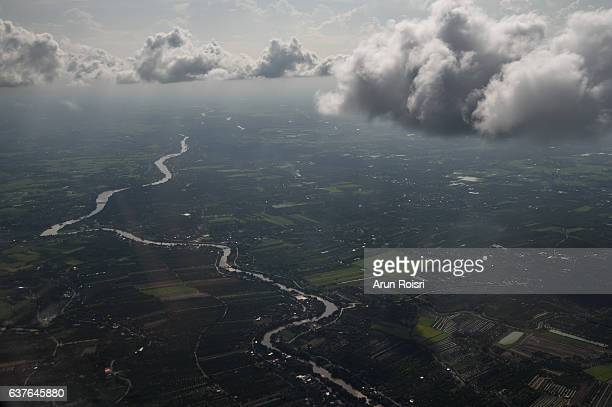 Cloudscape in sunny weather, white dense clouds floating over city and the land surface.