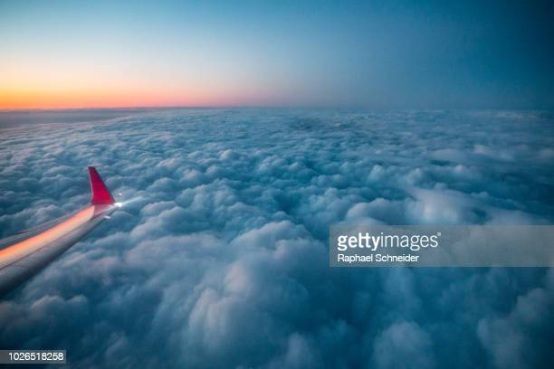 cloudscape in the evening from airplane window - airplane sky stock pictures, royalty-free photos & images